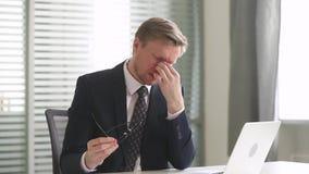 Stressed a surmené l'homme d'affaires enlevant des verres fatigués à partir de l'ordinateur banque de vidéos
