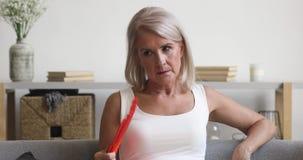 Stressed older woman breathing waving fan feeling heat at home
