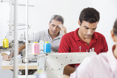 Stressed Tailor With Colleagues Working In Factory Royalty Free Stock Images