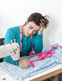 Stressed Tailor Leaning On Workbench Stock Image