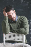 Stressed teacher man wearing stylish clothes in front a blackboard. stock photography