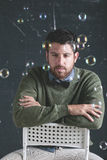 Stressed teacher man wearing stylish clothes in front a blackboard. Royalty Free Stock Photo