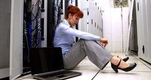 Stressed technician sitting on floor beside open server stock video