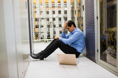 Stressed technician sitting in hallway stock image