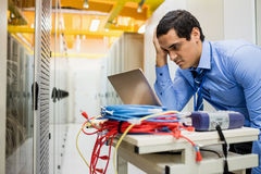 Stressed technician using laptop. In server room Stock Image