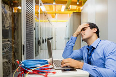 Stressed technician working laptop. In server room Royalty Free Stock Photography
