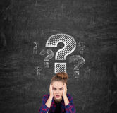 Stressed teen girl and big question mark. Stressed teen girl in a checkered shirt is sitting near a blackboard with a large question mark drawn on it Royalty Free Stock Images