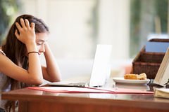 Stressed Teenage Girl Using Laptop On Desk At Home. With Head In Hands royalty free stock image