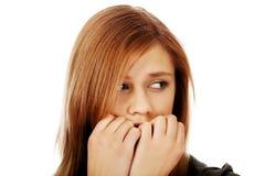 Stressed teenage woman biting nails Royalty Free Stock Image