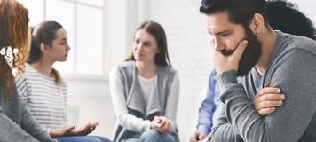 Stressed thoughtful man during sitting at rehab therapy. Meeting of support group. Stressed thoughtful men during sitting at rehab therapy, panorama royalty free stock image