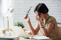 Tired of work. Stressed or tired business lady rubbing her eyes royalty free stock images