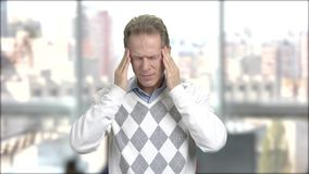 Stressed tired man having a bad headache. Mature man having terrible headache, window city background stock video footage