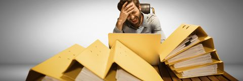 Stressed and tired man with lots of files table. Digital composite of Stressed and tired man with lots of files table Stock Photos
