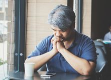 Stressed tired young Asian middle-aged man,elderly man take hand on head feeling depression and exhausted sitting by the window at. Coffee shop,grey hair man stock photos