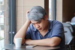 Stressed trött ung asiatisk medelålders man, gamal mantagandehand på huvudkänslafördjupning och utmattat sammanträde vid fönstret royaltyfria foton