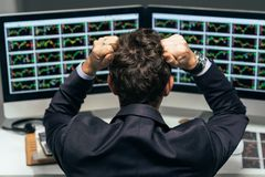 Stressed trader. Stock trader tearing out his hair from despair, rear view royalty free stock photo