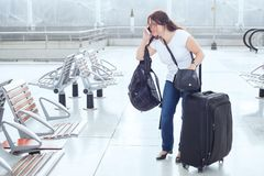 Stressed troubled woman in the airport. With plenty of bags and luggage Stock Photo