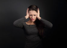 Stressed unhappy business woman closed ears the hands because no. T want the hear any sounds and noise on dark grey background Stock Photography