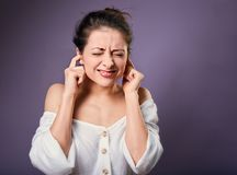 Stressed unhappy casual woman closed ears the fingers because not want the hear any sounds and noise. On purple background stock photography