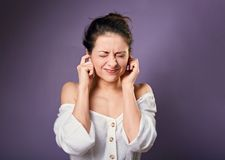 Stressed unhappy casual woman closed ears the fingers because not want the hear any sounds and noise. On purple background royalty free stock photos