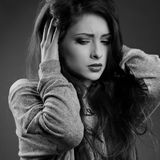 Stressed unhappy casual woman with headache in grey sweater hold. Ing the hands the head on dark shadow background. Closeup black and white portrait Stock Image