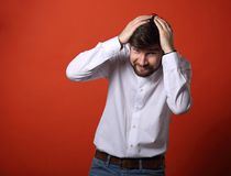 Stressed unhappy frightened bearded business man defends and hid. Ing the head his hands in white shirt on bright orange background Royalty Free Stock Photography