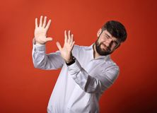 Stressed unhappy frightened bearded business man defends himself. The hands in white shirt on bright orange background Stock Image