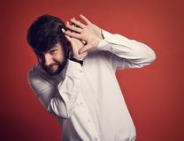 Stressed unhappy frightened bearded business man defends himself. The hands in white shirt on red background. Closeup toned portrait Stock Photography