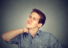 Stressed unhappy young handsome man with bad neck pain. On grey wall background. Negative human emotion facial expression Stock Images