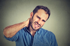 Stressed, unhappy young handsome man with bad neck pain. Portrait stressed, unhappy young handsome man with bad neck pain, after long hours of work studying Royalty Free Stock Photos