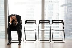 Stressed upset businessman sitting on chair, received bad news. Royalty Free Stock Photo