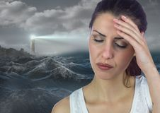 Stressed upset woman next to hopeful lighthouse. Digital composite of Stressed upset woman next to hopeful lighthouse Stock Photography