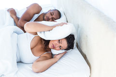 Stressed wife sleeping besides snoring husband Stock Photos