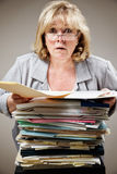 Stressed woman. Mature woman overwhelmed by the stack of paperwork Royalty Free Stock Photos