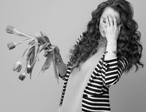 Stressed woman against background with wilted flowers. Stressed stylish woman in striped jacket against background with wilted flowers stock images