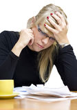 Stressed woman with bills. Portrait of stressed young woman holding head with pile of bills and cup of tea or coffee; white studio background with clipping path Stock Photo