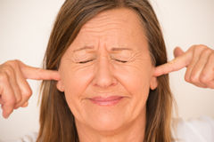 Stressed Woman blocking ears with finger Stock Images