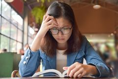 Stressed Woman in Blue shirt reading a book. Stock Photography