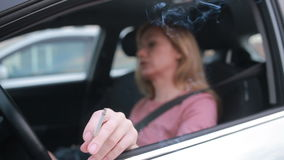 Stressed woman in the car smoking cigarette and checking the time. traffic jam stock video footage