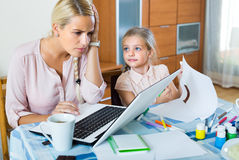 Stressed woman with child working from home Royalty Free Stock Photo