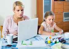 Stressed woman with child working from home Stock Images