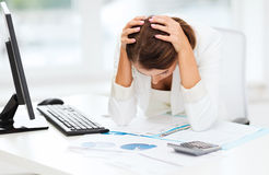 Stressed woman with computer, papers, calculator Royalty Free Stock Photography