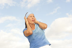 Stressed Woman covering ears from noise outdoor Stock Images