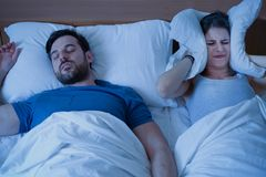 Stressed woman covering ears with a pillow as she is annoyed by the snoring of her boyfriend. Man snoring in the bed because of night apnoea sleep disorder royalty free stock photo