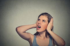 Stressed woman covering her ears looking up stock images