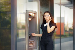Stressed Woman with credit card at ATM Stock Image