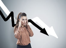 Stressed woman and declining graphs on gray wall Royalty Free Stock Photography