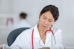 Stressed woman doctor sitting in office Royalty Free Stock Image