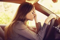 Stressed woman driver sitting inside her car. Stressed young woman driver sitting inside her car frustrated with heavy traffic royalty free stock images