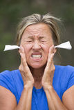 Stressed woman with earplugs against noise outdoor Royalty Free Stock Photos